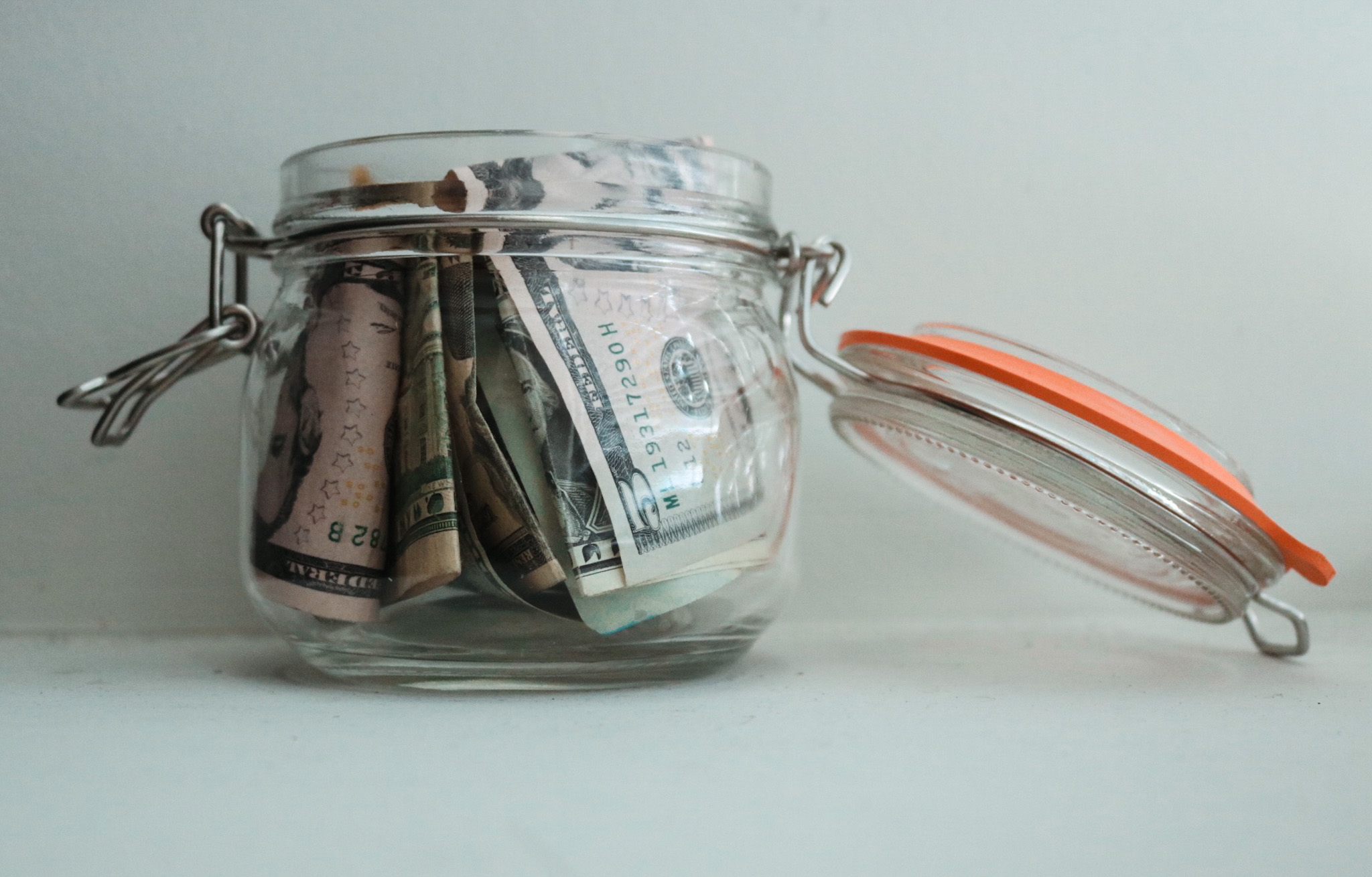 A mason jar over flowing with money sits on a white background
